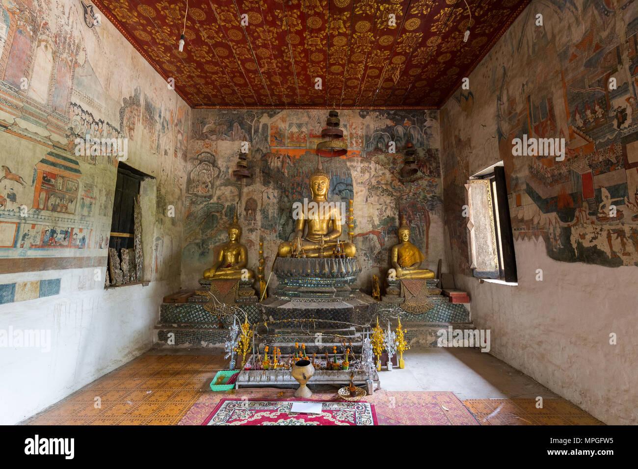 Murales, altare e statue di Buddha all'interno di Wat Pa Huak tempio a Luang Prabang, Laos. Immagini Stock