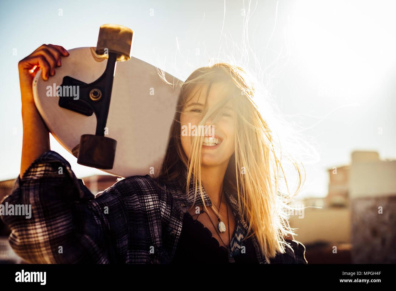 Bella bionda caucasiamo modello donna libera con uno skateboard nella retroilluminazione sole al tramonto. libertà e indipendenza il concetto della gioventù in Tenerife. Capelli su Immagini Stock