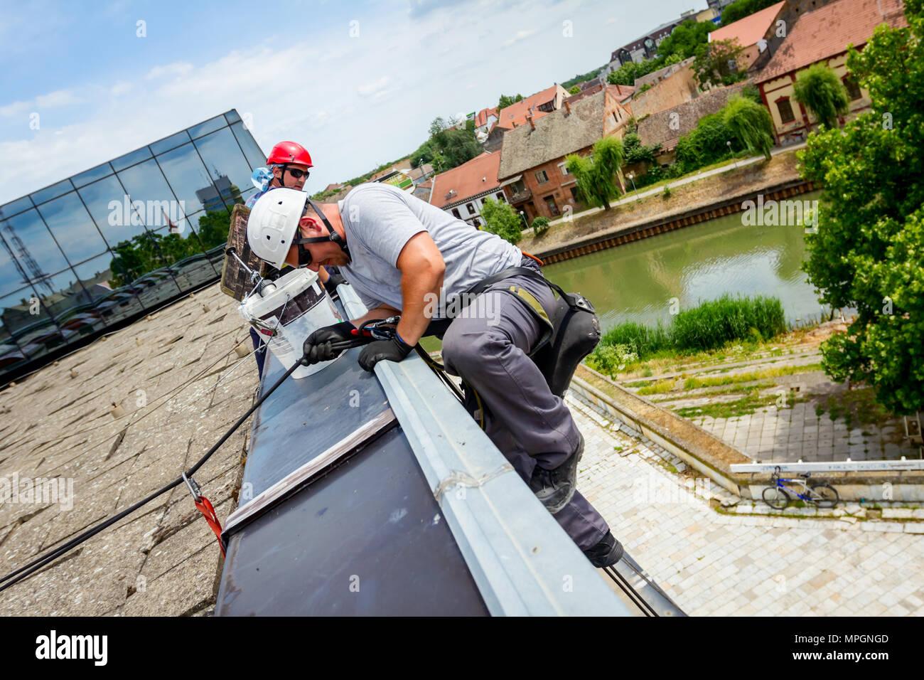 Scalatore industriali, alpinista, si passa sopra il bordo del tetto. Egli è salita verso il basso per il lavaggio di edificio. Immagini Stock