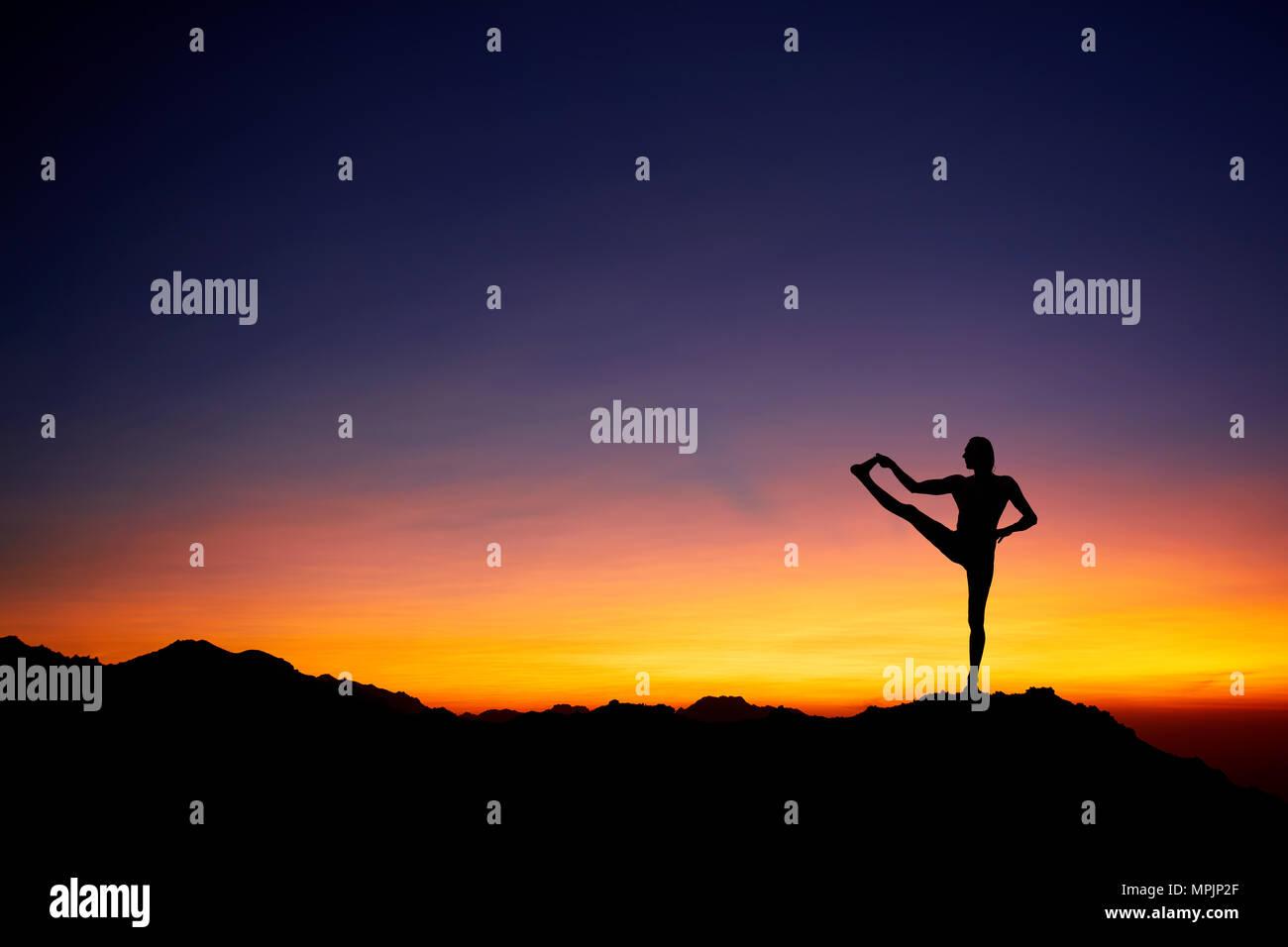 Montare l'uomo in silhouette fare yoga equilibrio pongono in corrispondenza di un bel colore arancione tramonto sullo sfondo del cielo Immagini Stock