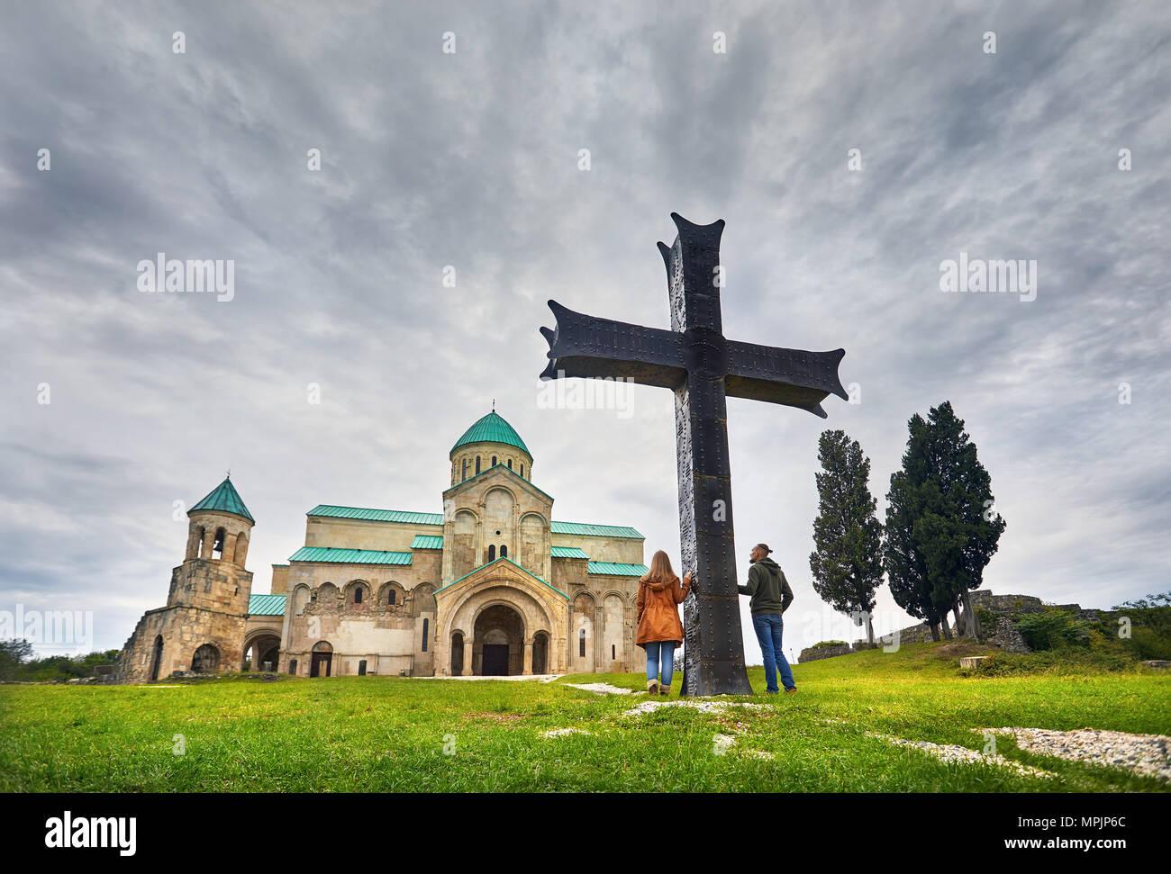 Turista giovane vicino al grande croce davanti alla chiesa di Bagrati a cielo nuvoloso in Kutaisi, Georgia Immagini Stock