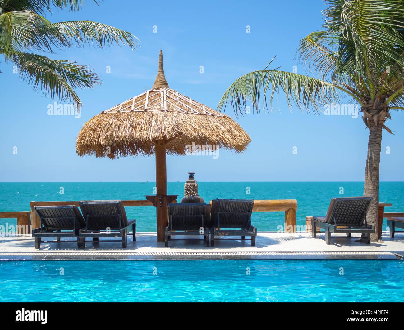 Come Costruire Un Ombrellone Di Paglia.Terrazza Vista Mare Sdraio Sotto Gli Ombrelloni Di Paglia Con Palme Di Cocco E Piscina Sul Cielo Azzurro Sfondo Concetto Di Estate Foto Stock Alamy