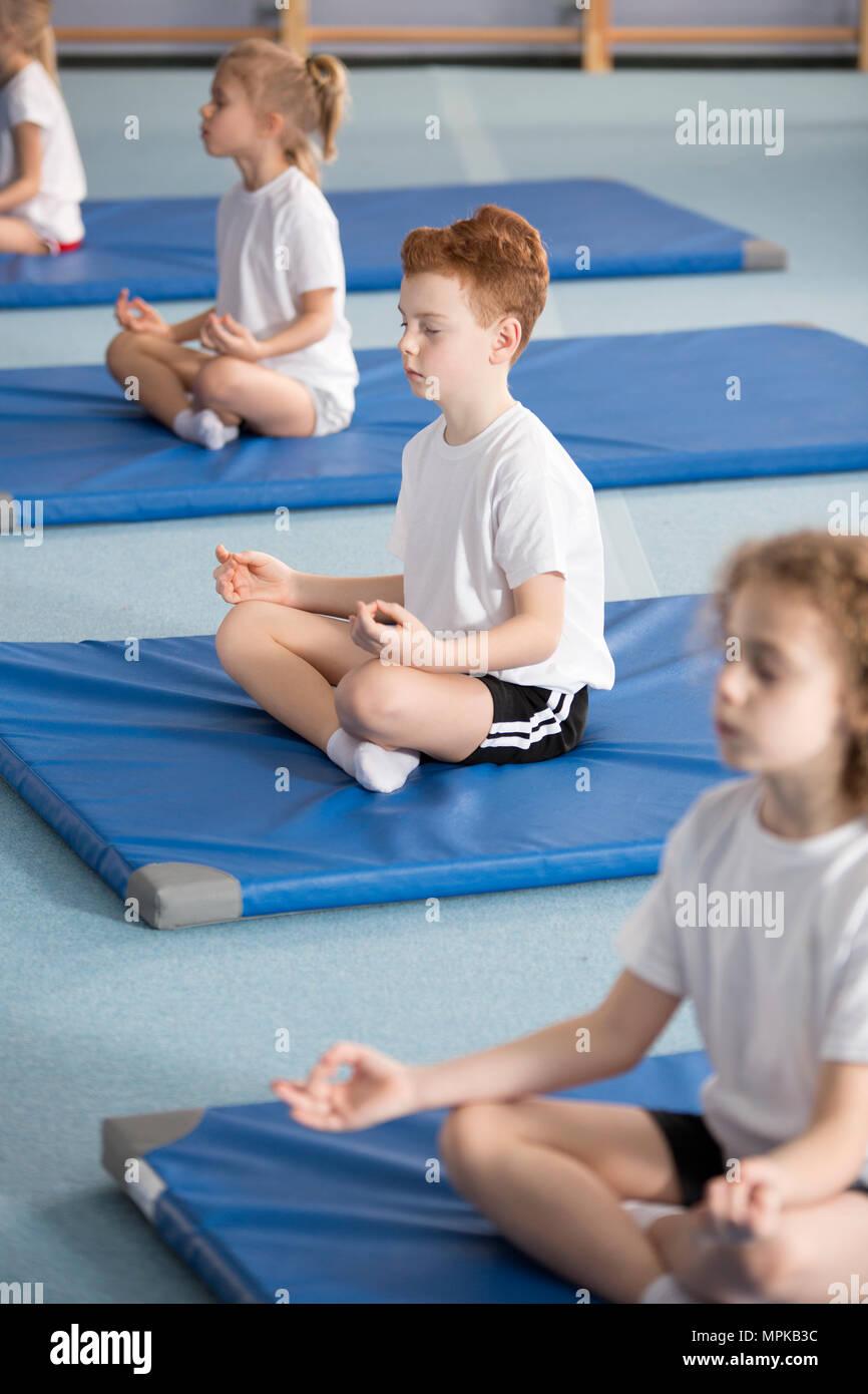 Scuola elementare allievo e altri bambini seduti sulle stuoie con le gambe incrociate e gli occhi chiusi in meditazione rilassante classe Immagini Stock