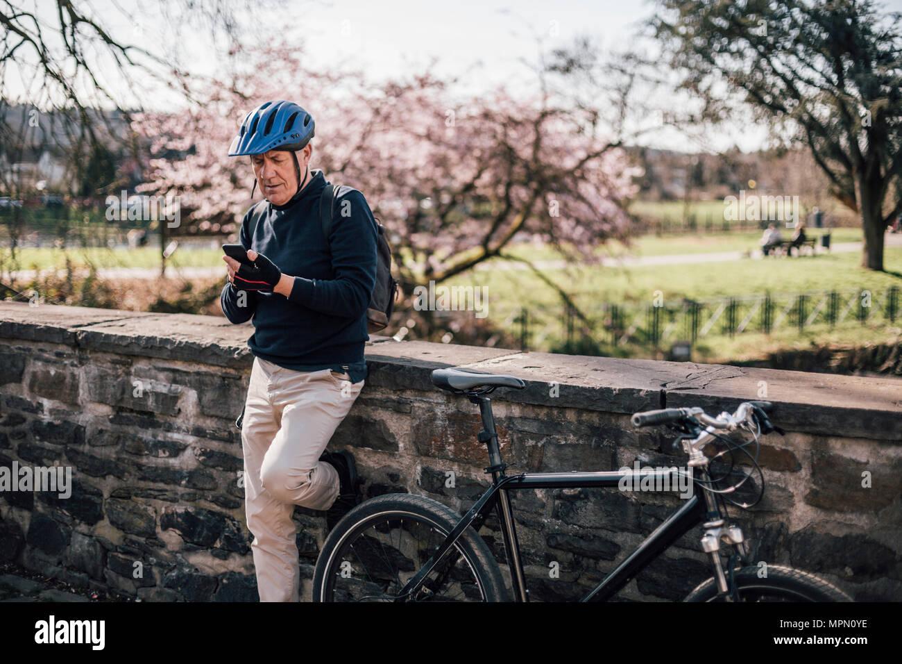 L'uomo anziano con il ciclismo casco utilizza lo smartphone Immagini Stock