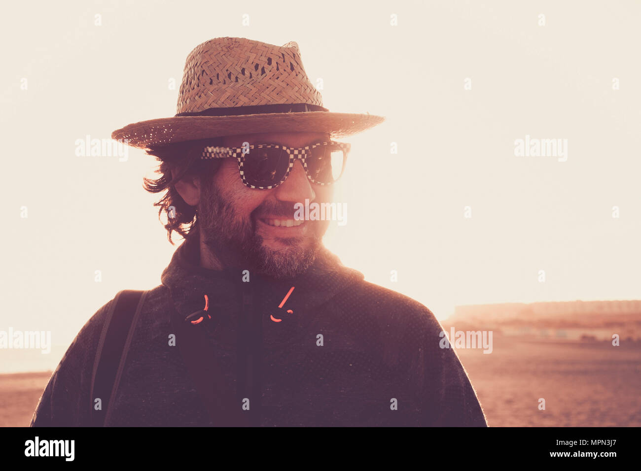 Smile uomo guarda al suo fianco in un deserto ritratto outdoor in Tenerife. indossare un cappello e occhiali da sole con retroilluminazione. Immagini Stock