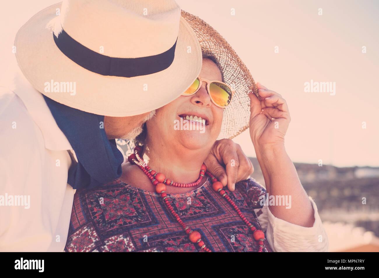 Adulti soggiorno insieme con il bacio e abbraccio sotto il sole con cappelli e occhiali da sole e collana. Il vero amore per sempre insieme concetto Immagini Stock