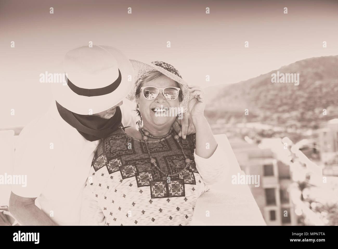 Coppia vintage con cappello sorridono e si coccolano all'aria aperta in terrazza in estate Foto Stock