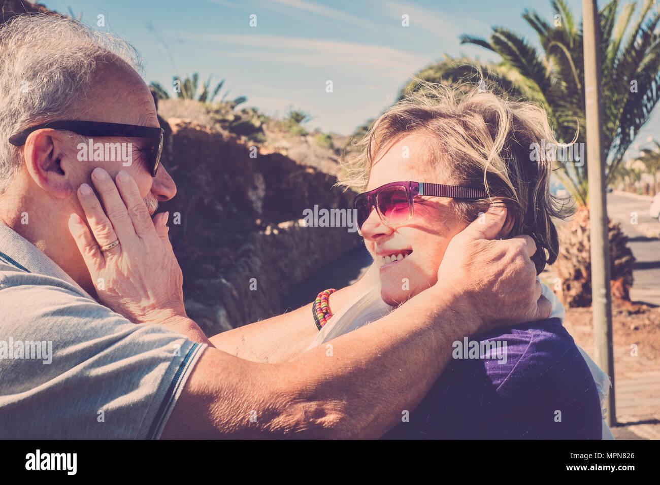 Coppia di anziani con i capelli bianchi, coccole e abbracci ogni altro all'aria aperta sotto il sole di Tenerife Immagini Stock