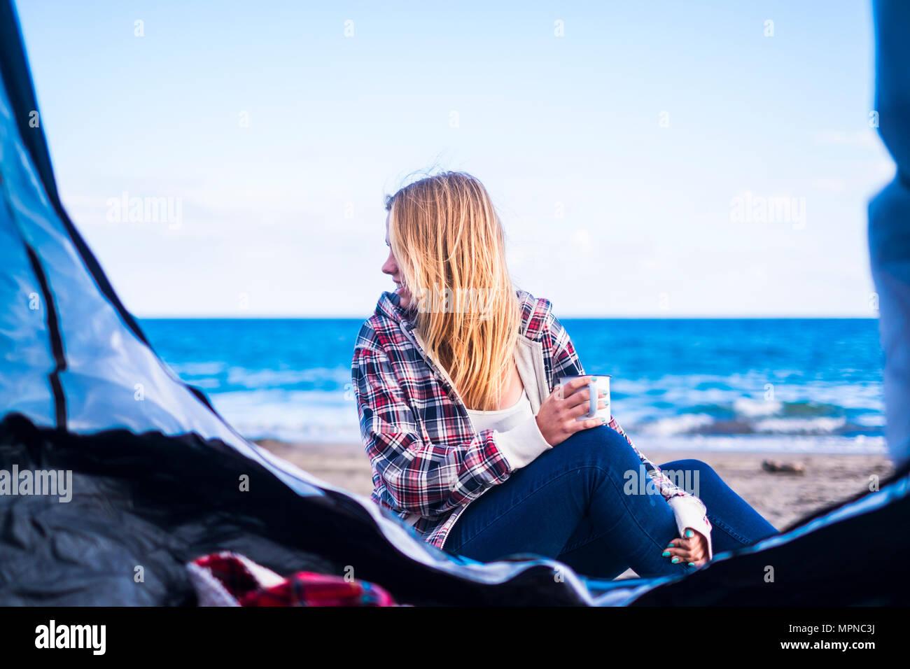 Forme alternative di vita e il concetto di vacanza per bionda ragazza carina sedersi guardando l'oceano sulla porta della sua tenda. Tenerife locetion. Immagini Stock