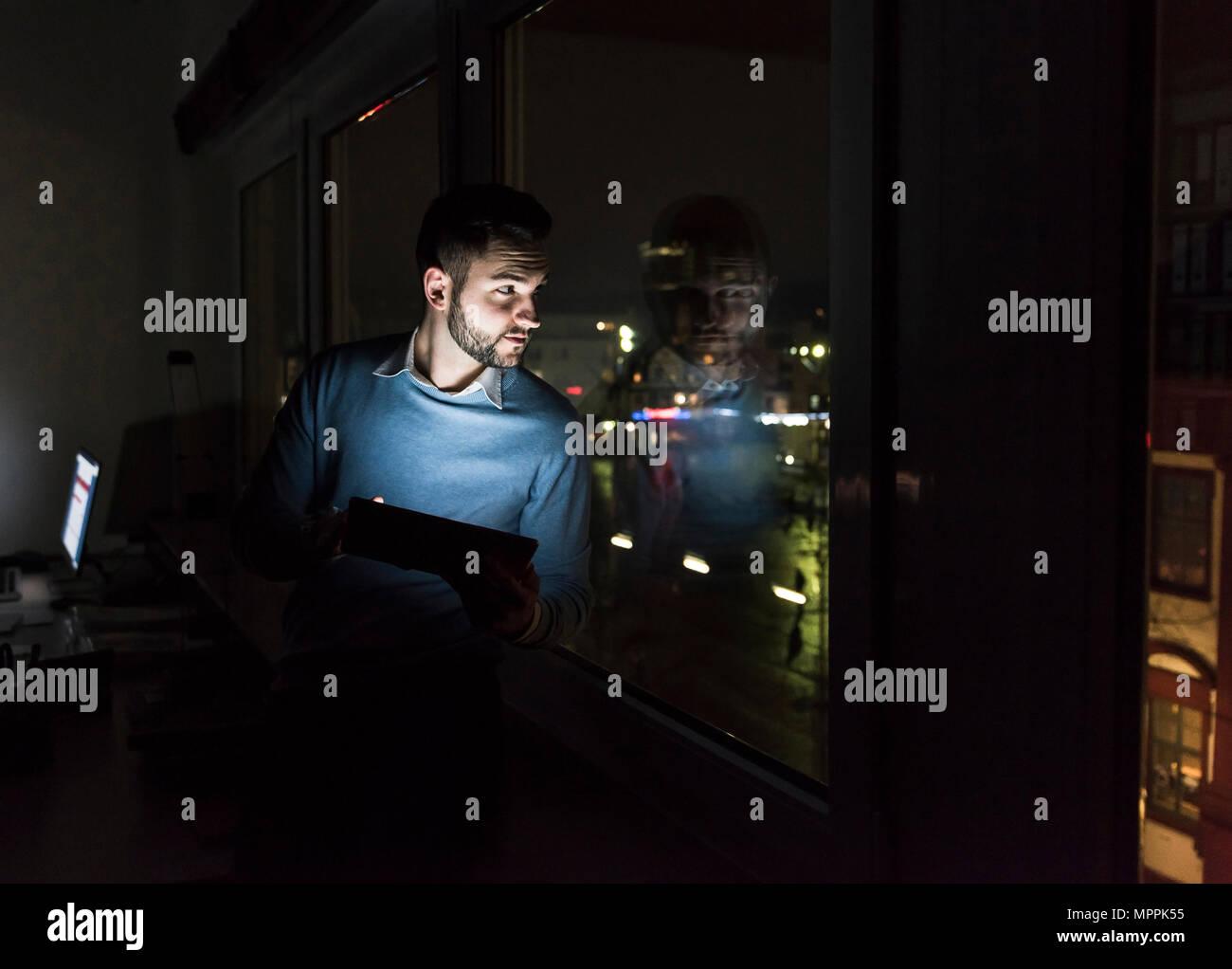 Imprenditore seduto con la compressa sul davanzale in office di notte guardando fuori della finestra Immagini Stock