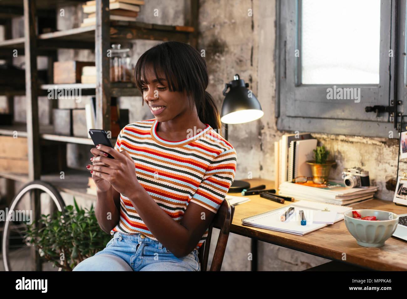 Sorridente giovane donna seduta di fronte a scrivania in un loft guardando al telefono cellulare Immagini Stock