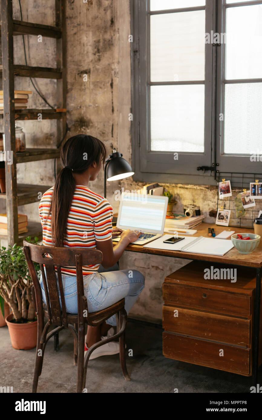 Vista posteriore della giovane donna seduta alla scrivania in un loft lavorando sul computer portatile Immagini Stock