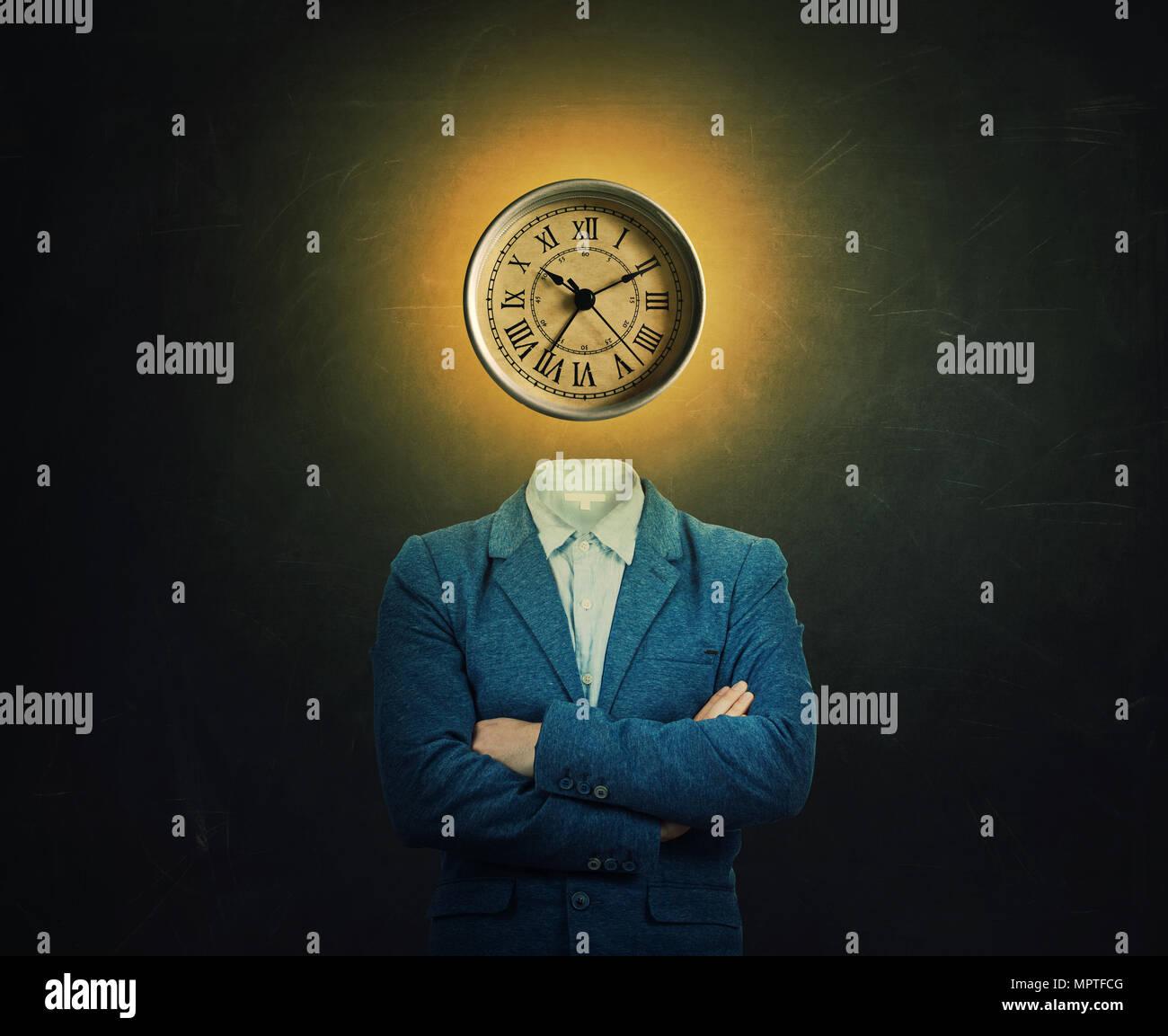 Surreale immagine di un serio professore con due mani incrociate e un orologio al posto della sua testa sulla lavagna sfondo. Il concetto di tempo in educativo Immagini Stock