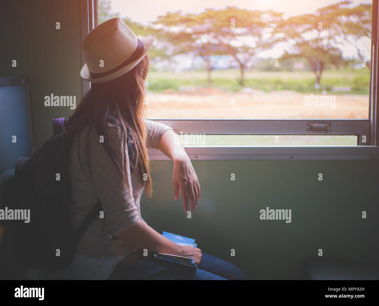 Giovane donna graziosa viaggiando con il treno classico seduto vicino alla finestra a guardare all'esterno. Vacanza e tavel concetto. Immagini Stock