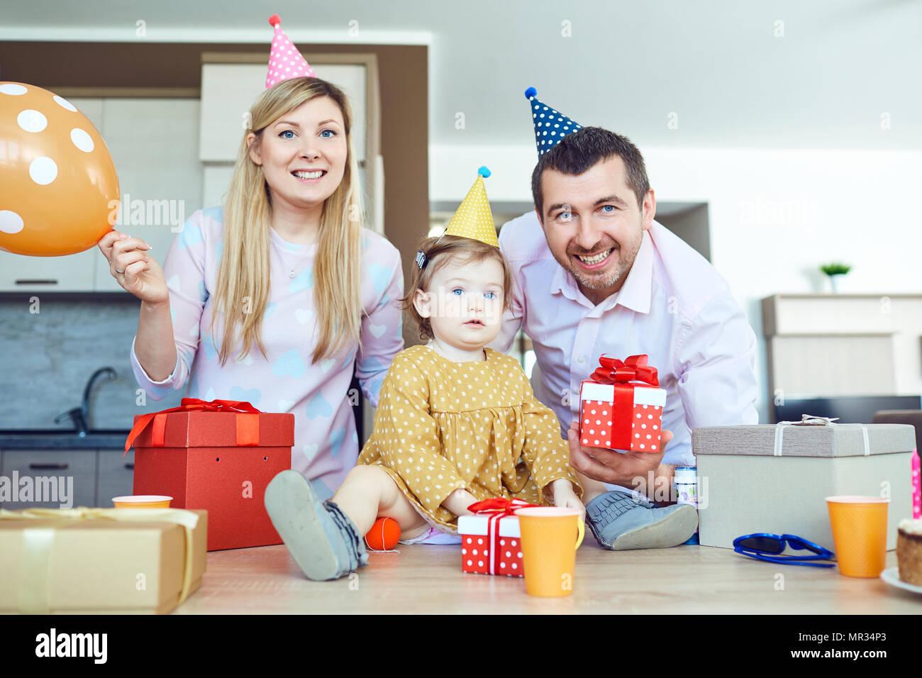 Una famiglia con una torta si congratula con un bambino felice per il suo compleanno Immagini Stock