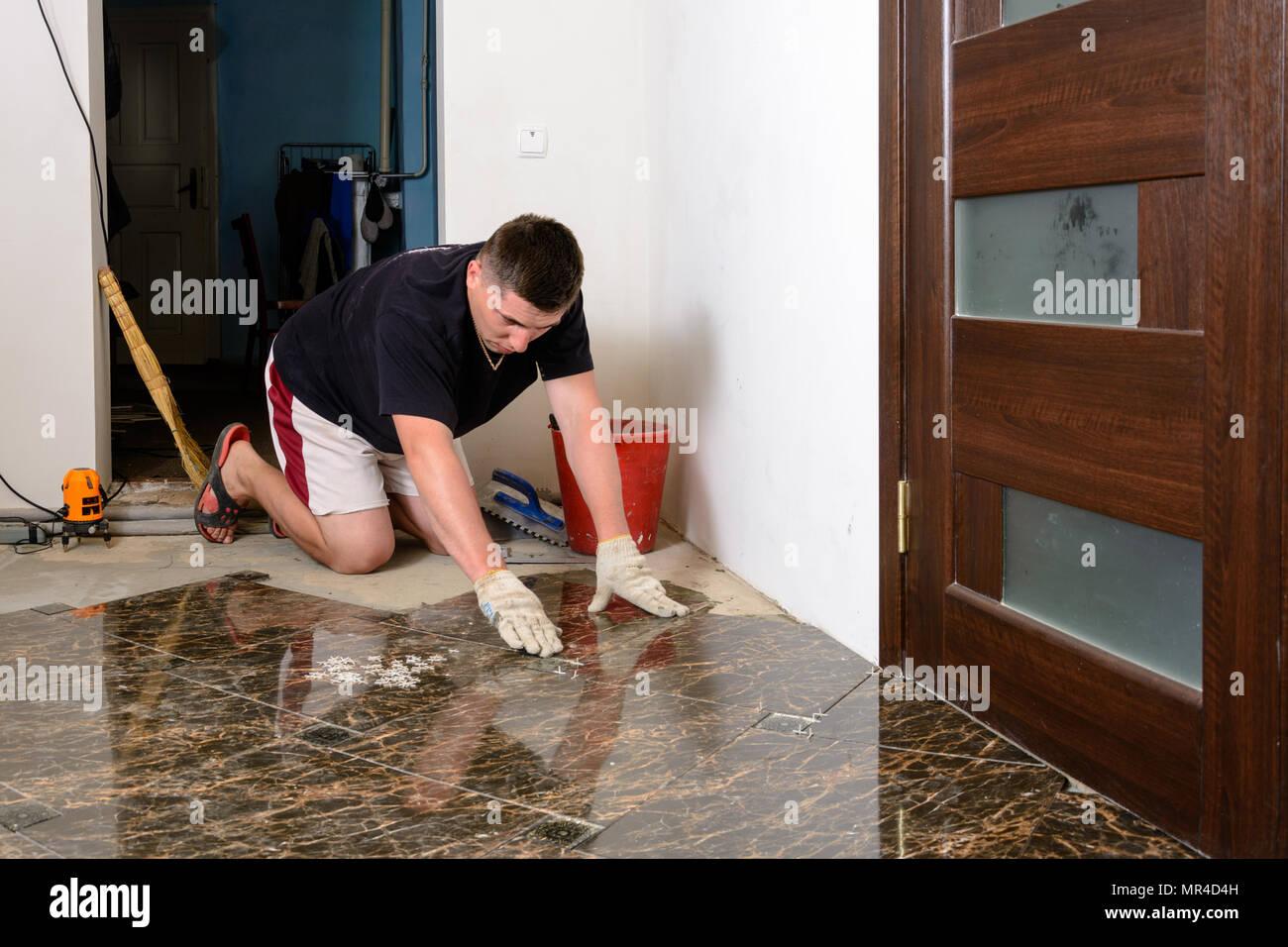 L uomo immissione ceramiche piastrelle del pavimento in posizione