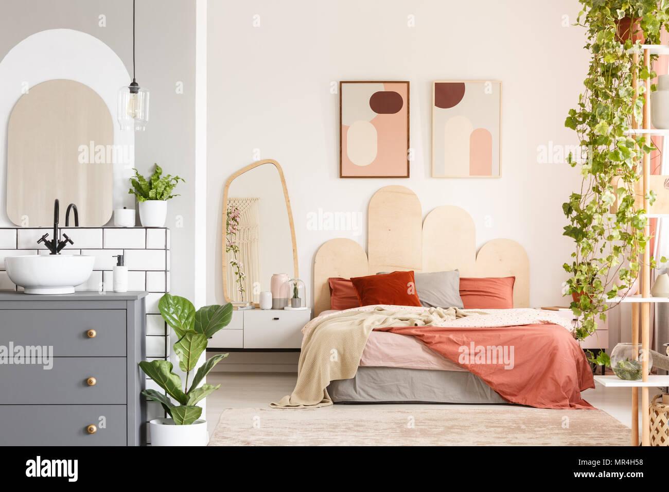 Orange cuscini sul letto accanto a uno specchio in camera da ...