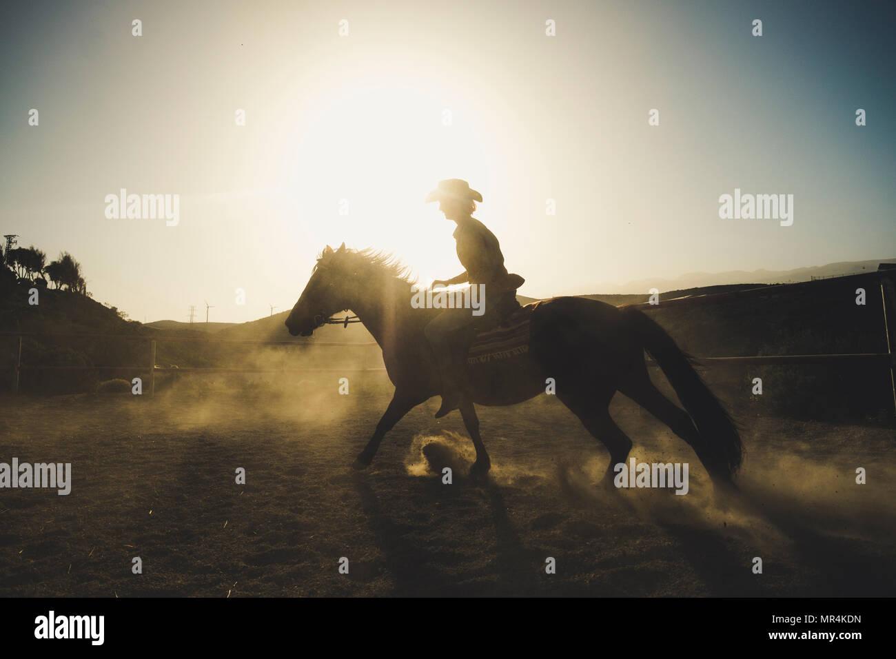 Bella ragazza andare a cavallo in silhouette e retroilluminazione con la sunflare e polvere dal suolo. epico ed eroi immagine per velocità e cowbot vita e annuncio Immagini Stock