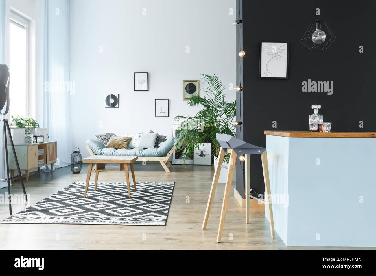Tavolo in legno in monocromatico e spazioso salotto con divano e