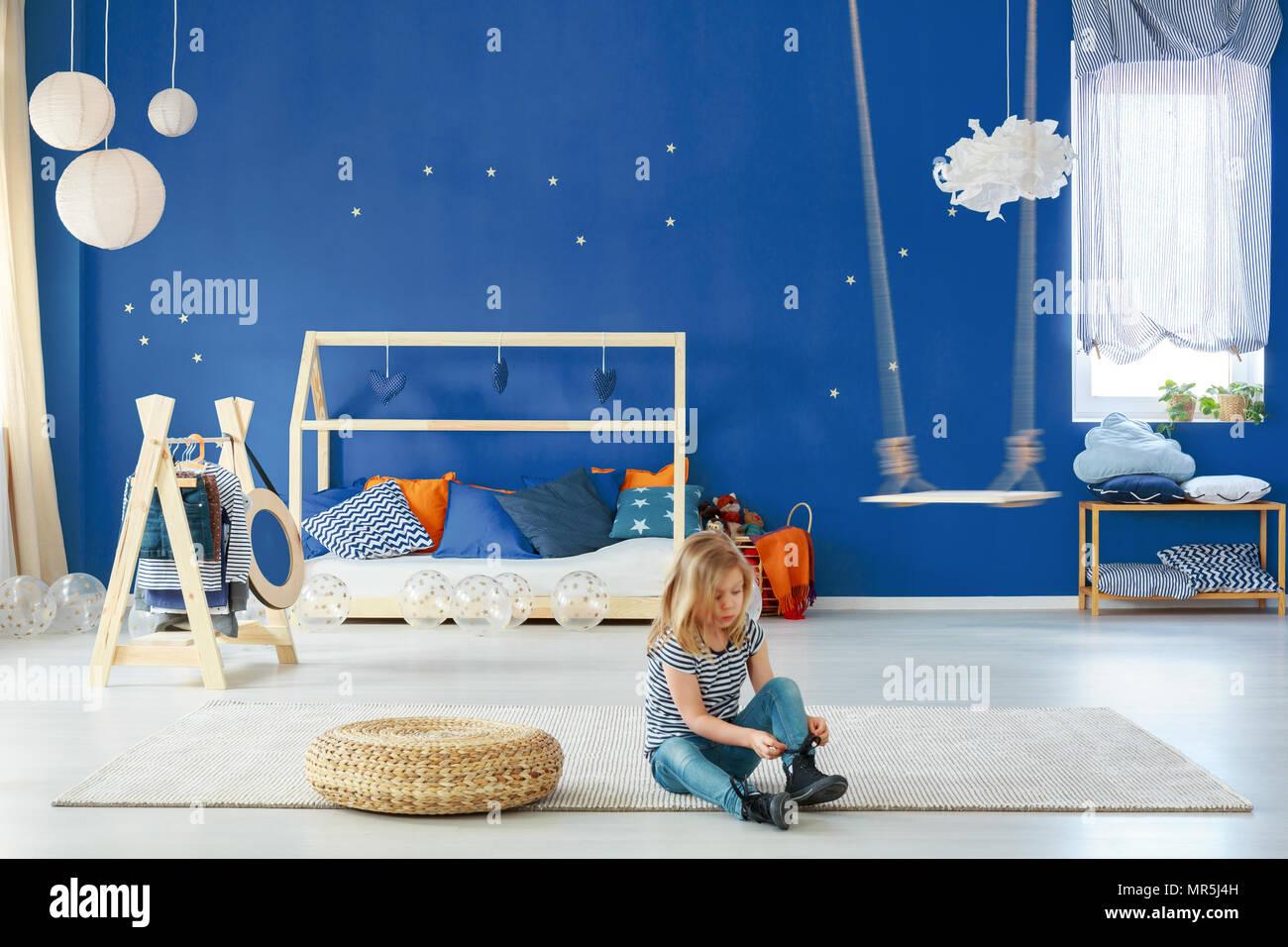 Ragazza camera da letto con parete blu, swing, portabiti e letto ...