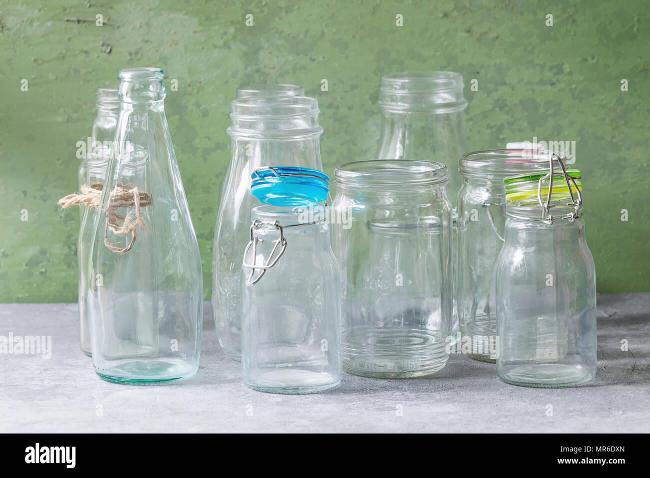 Varietà di diversa forma vuoto aperto le bottiglie di vetro con e senza coperchi permanente sulla tabella grigia con parete verde come sfondo. Immagini Stock
