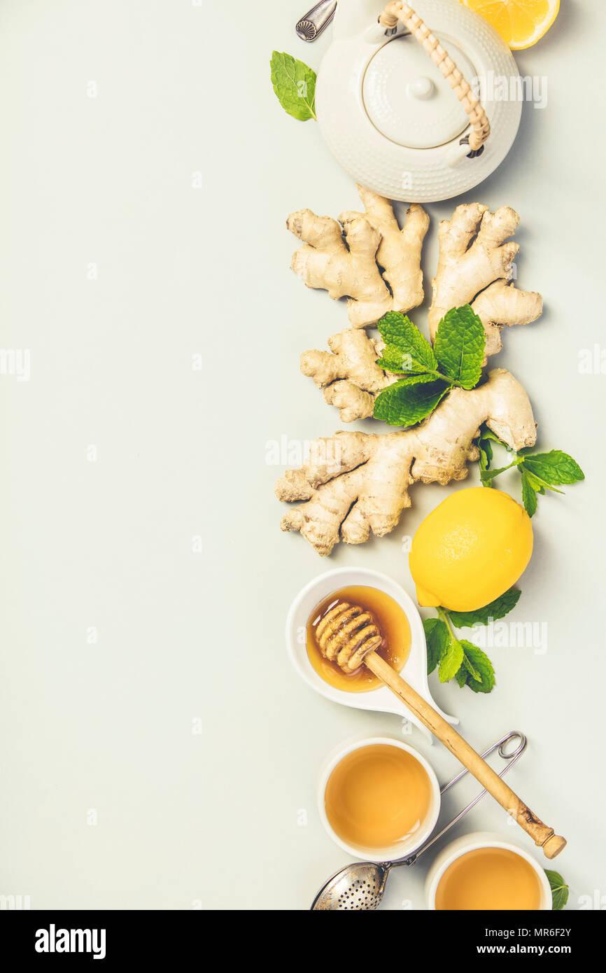 Il tè allo zenzero con il limone, il miele e le foglie di menta sul cemento grigio Sfondo. Vista superiore, laici piatta Immagini Stock
