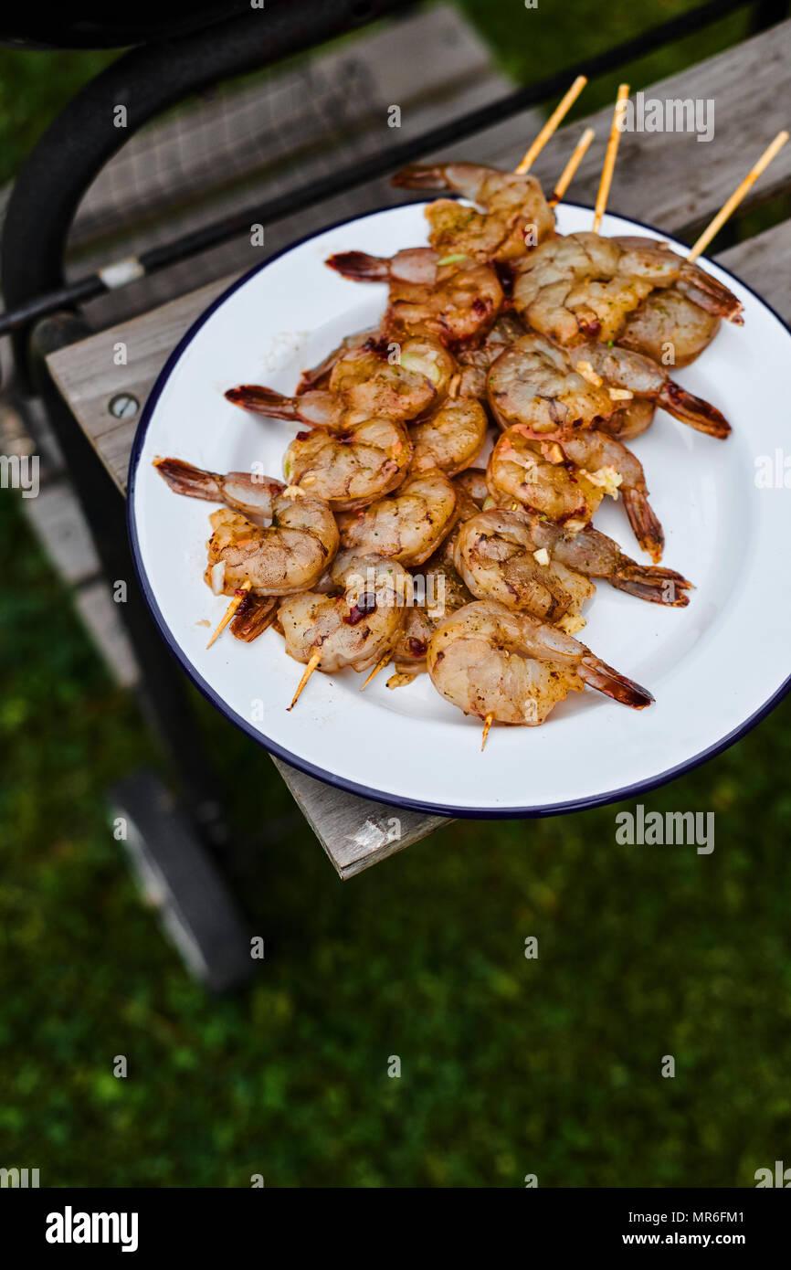 Alta Vista angolare della piastra di gamberi alla griglia su spiedini raffreddamento mediante il lato del barbecue Immagini Stock