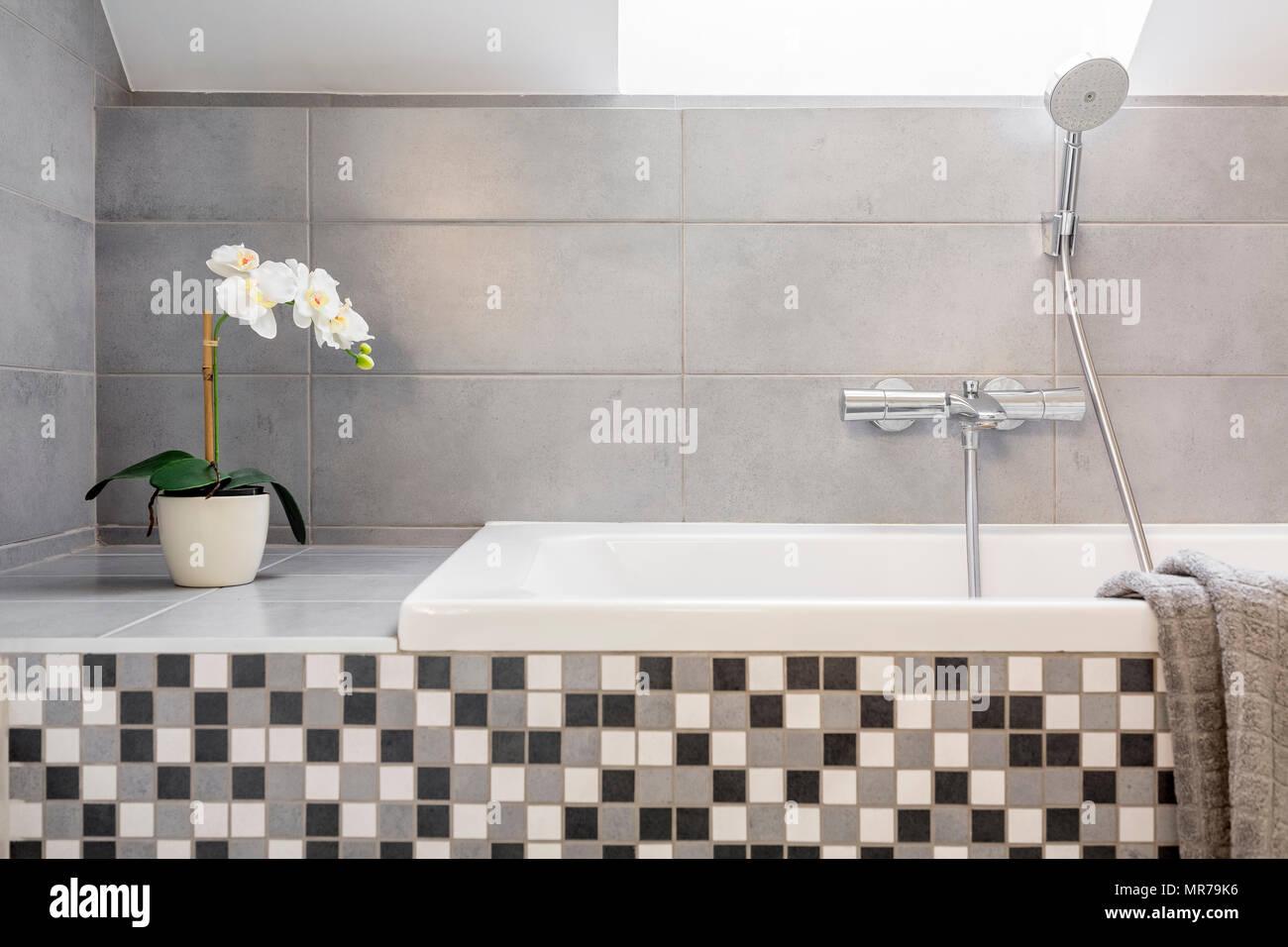 Grigio a bagno con piastrelle a mosaico e vasca da bagno foto