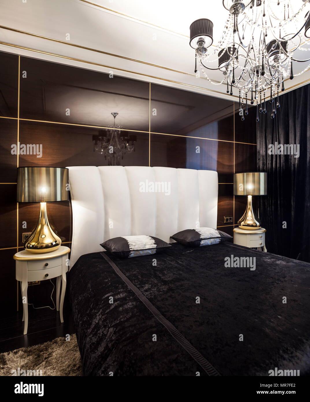 Elegante camera da letto letto nero con testiera bianco e lampadari ...