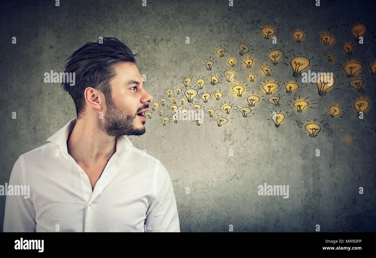 Erudito giovane uomo parlando diffondere idee brillanti con lampadine esce dalla sua bocca aperta Immagini Stock