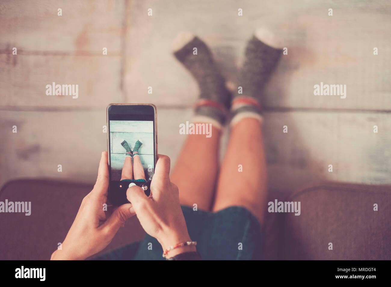 Bella donna caucasica scattare foto con il cellulare per le sue gambe contro la parete con belle e divertenti calzini. home stile di vita alternativo e indepe Immagini Stock