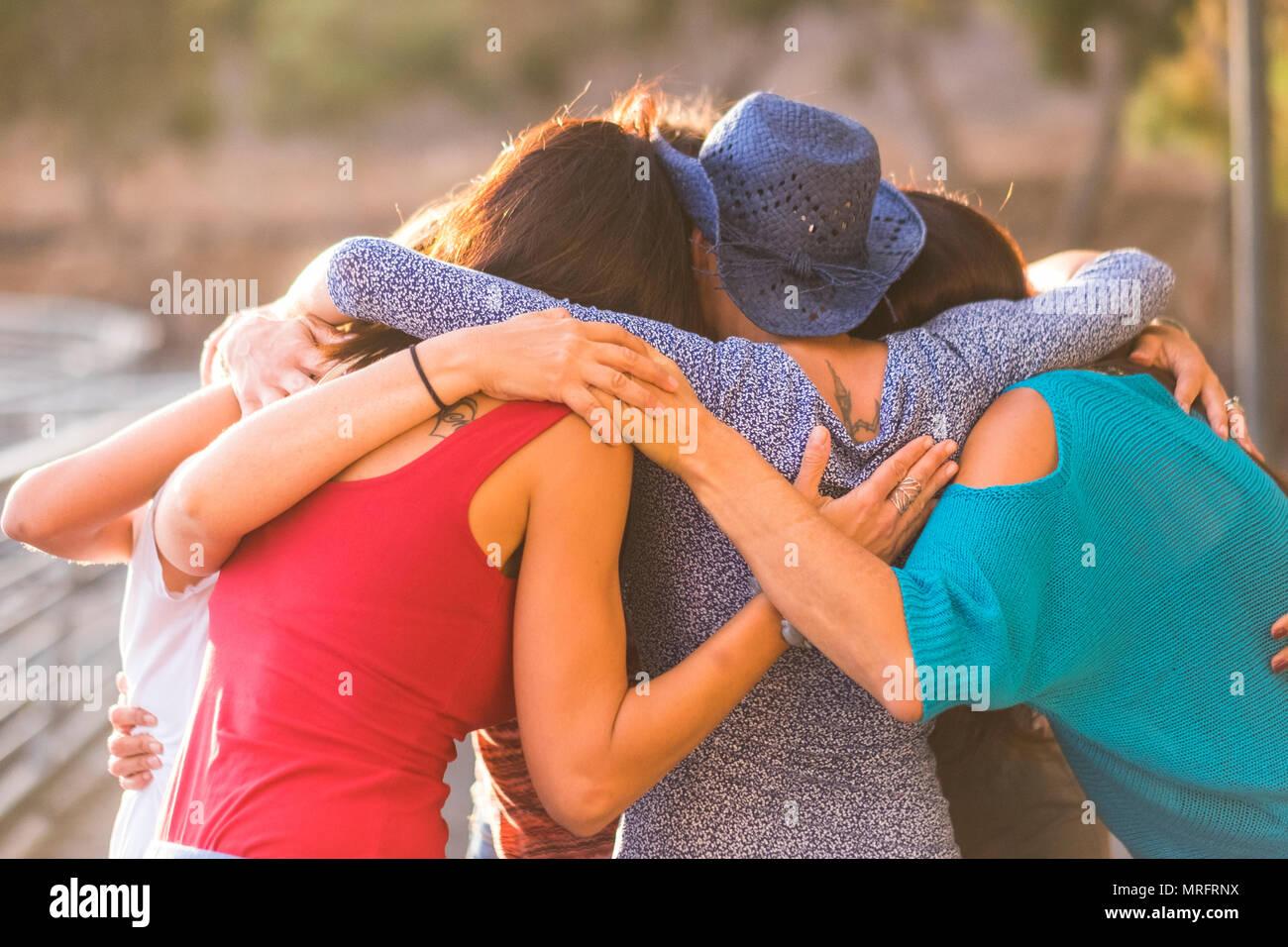 Unione tutti compresi come un lavoro di squadra e il gruppo di amici animali femmine 7 belle donne abbraccio tutti insieme sotto la luce del sole e al tramonto per amicizia e r Immagini Stock