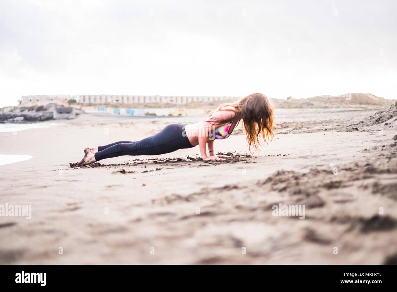 Yoga e Pilates resto forte posizione di resistere e di essere duro. bella giovane signora facendo fitness in spiaggia in outdoor le attività per il tempo libero. sabbia e lonely p Immagini Stock