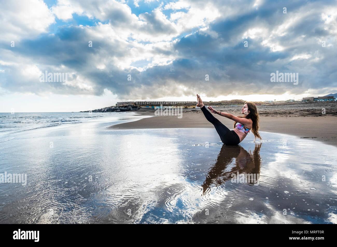 Fitness Pilates hanno cura del resto del corpo e la posizione di soggiorno per la giovane donna caucasica in riva alla spiaggia. scenic immagine per la salute del corpo concetto. yo Immagini Stock