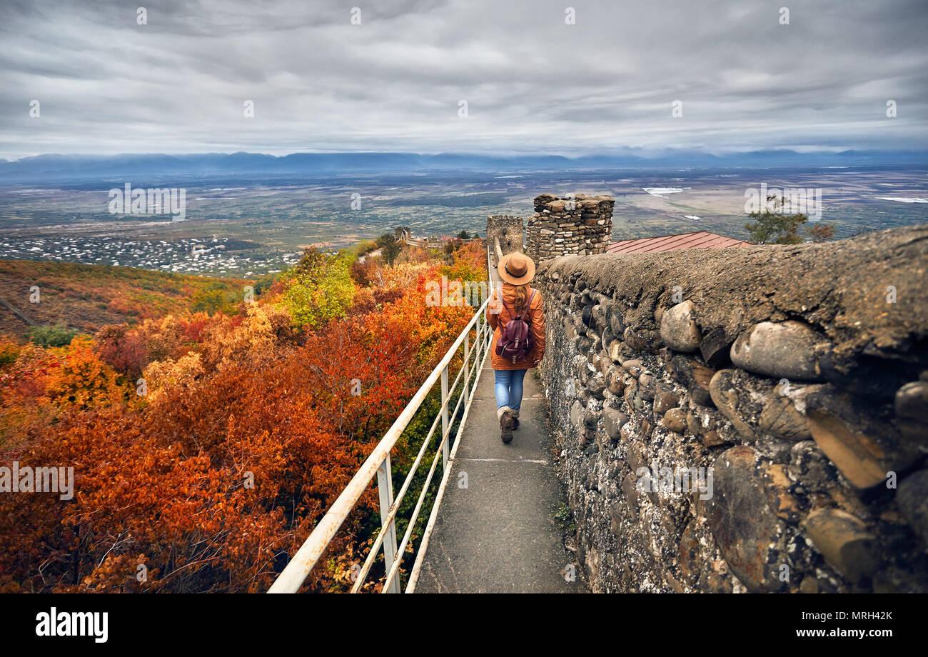 Donna turistiche in marrone cappello e zainetto passeggiando lungo le antiche mura della città con vista a valle Alazani in autunno in Signagi, Georgia Immagini Stock