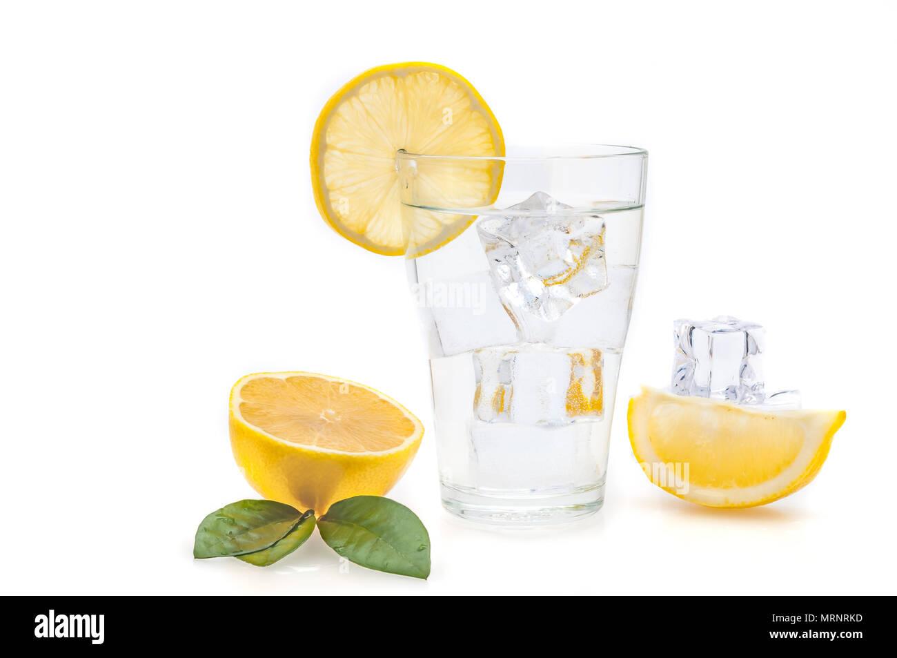 Acqua e limone e cubetti di ghiaccio in un bicchiere. Le fette di limone e lino accanto a un vetro. Immagini Stock