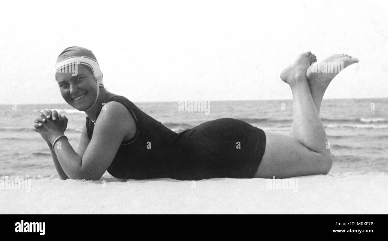 492801460865 Moda, costume da bagno, donna sdraiata sulla spiaggia con il costume da  bagno e