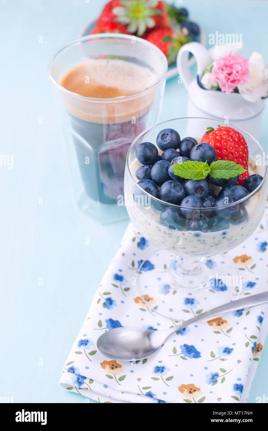 Un bicchiere di caffè e budino chia con mirtilli e fragole per la colazione. Vegetariano cibo sano. Sfondo blu. Tovagliolo con fiori e fiori in un vaso. Colori luminosi. Immagini Stock