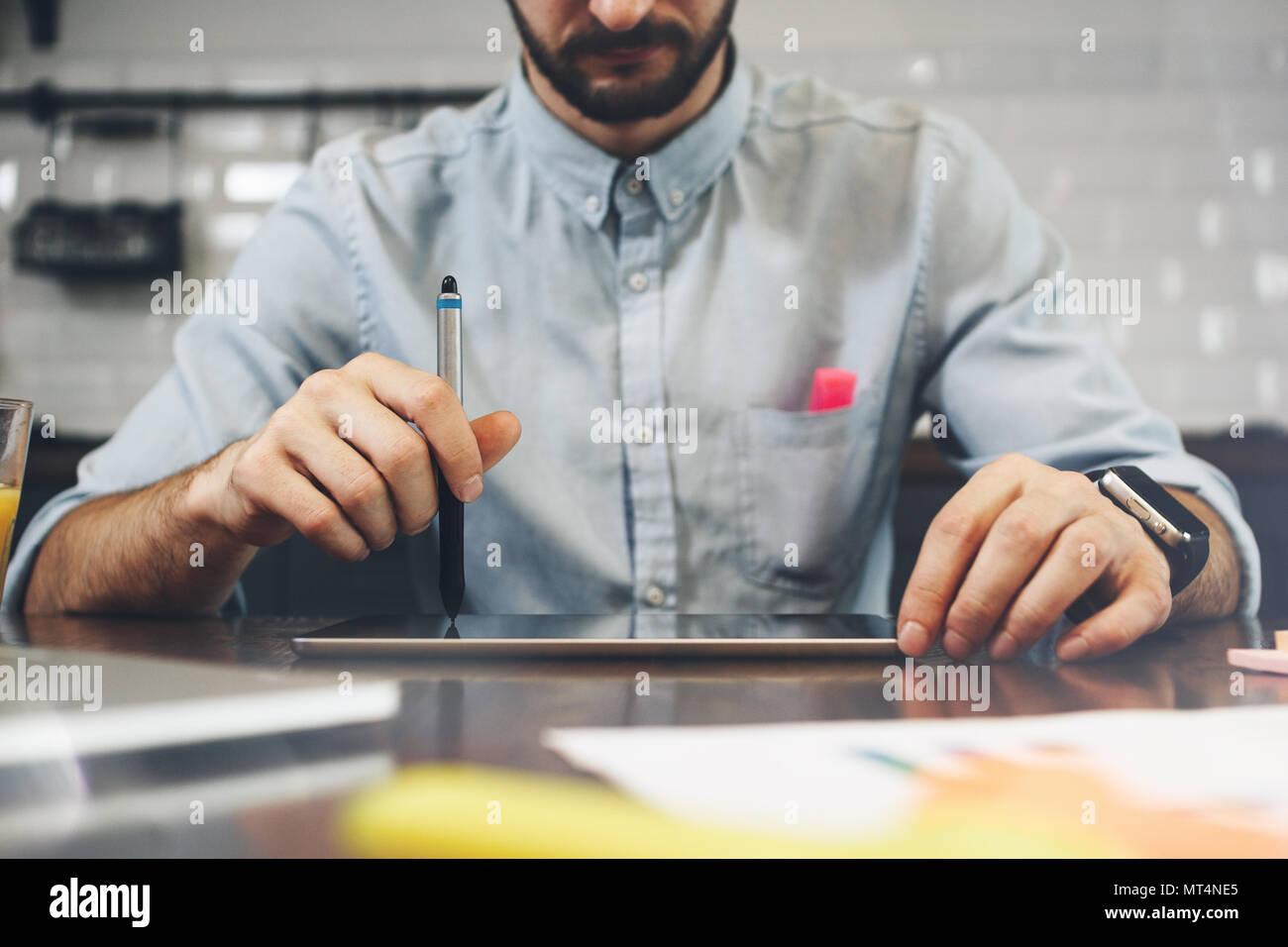 Uomo Barbuto utilizzando tablet per la conversazione video in ufficio moderno. Concetto di giovani uomini di affari che lavorano a casa. Uomo Barbuto uso generico giro di design Immagini Stock