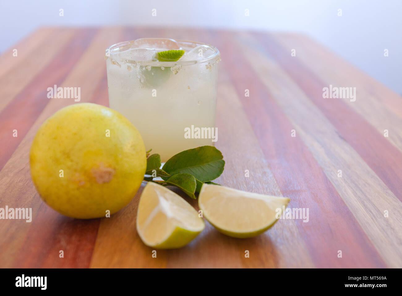 Key Lime margarita guarnita con lime fresco in una barra di vetro tabella Immagini Stock