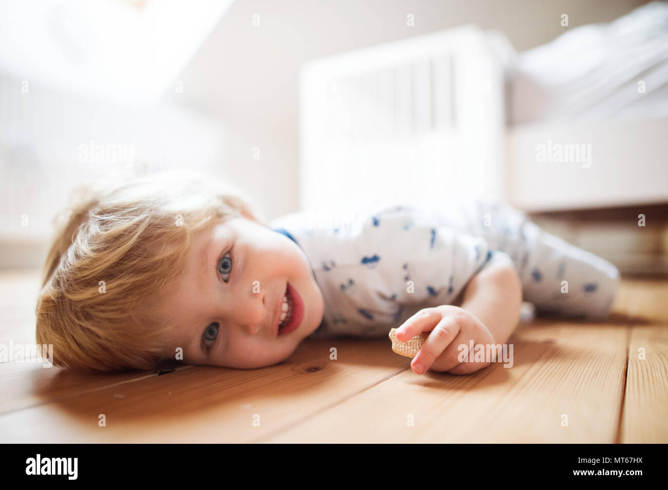 Un bimbo piccolo ragazzo sul pavimento in camera da letto a casa. Immagini Stock