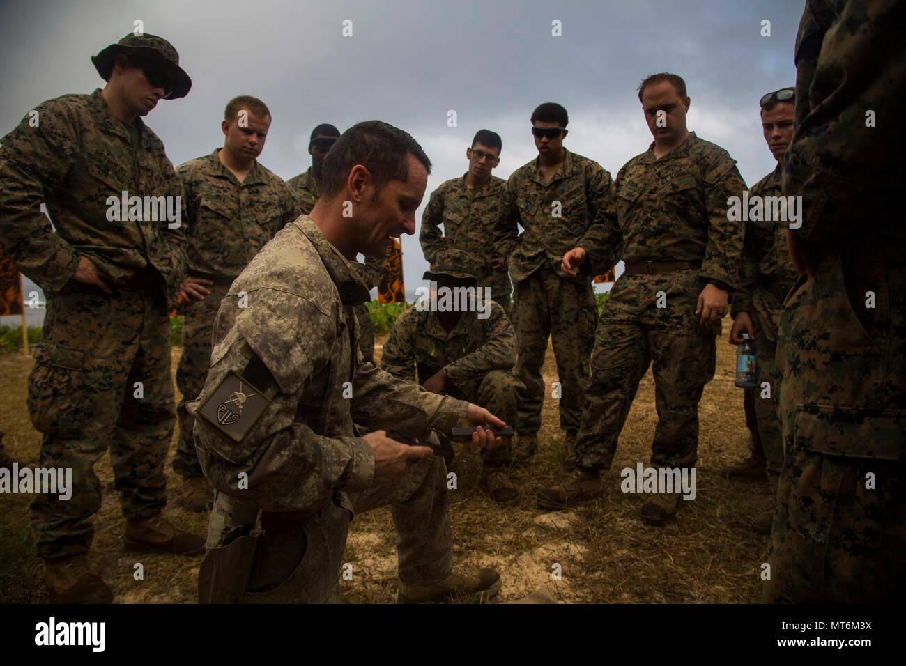 Stati Uniti Marines con 3° Battaglione 4 Marines attaccata alla Task Force Koa Moana 17, raccogliere intorno alla Nuova Zelanda Army Sgt. Il Mag. Paolo Buckley come spiega la glock 17 weapon system durante l'esercizio TAFAKULA, sull isola di Tongatapu, Tonga, luglio 21, 2017. Esercizio TAFAKULA è progettata per rafforzare le strutture militari e le relazioni tra comunità tra Tonga di Sua Maestà delle Forze Armate, Esercito francese della Nuova Caledonia, Nuova Zelanda forza di difesa e le forze armate degli Stati Uniti hanno. (U.S. Marine Corps photo by MCIPAC combattere lancia fotocamera Cpl. Juan C. Bustos) Foto Stock