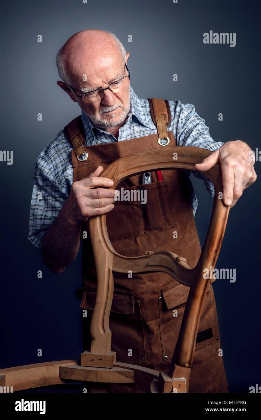 Senior artigiano caucasica controllare sedia incompiuto studio shot Foto Stock