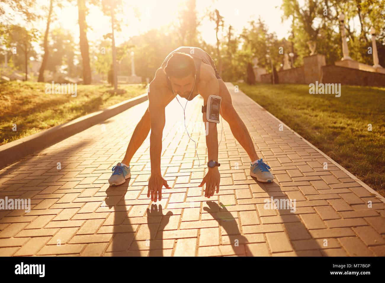 Giovane uomo facendo stretching nel parco. Immagini Stock