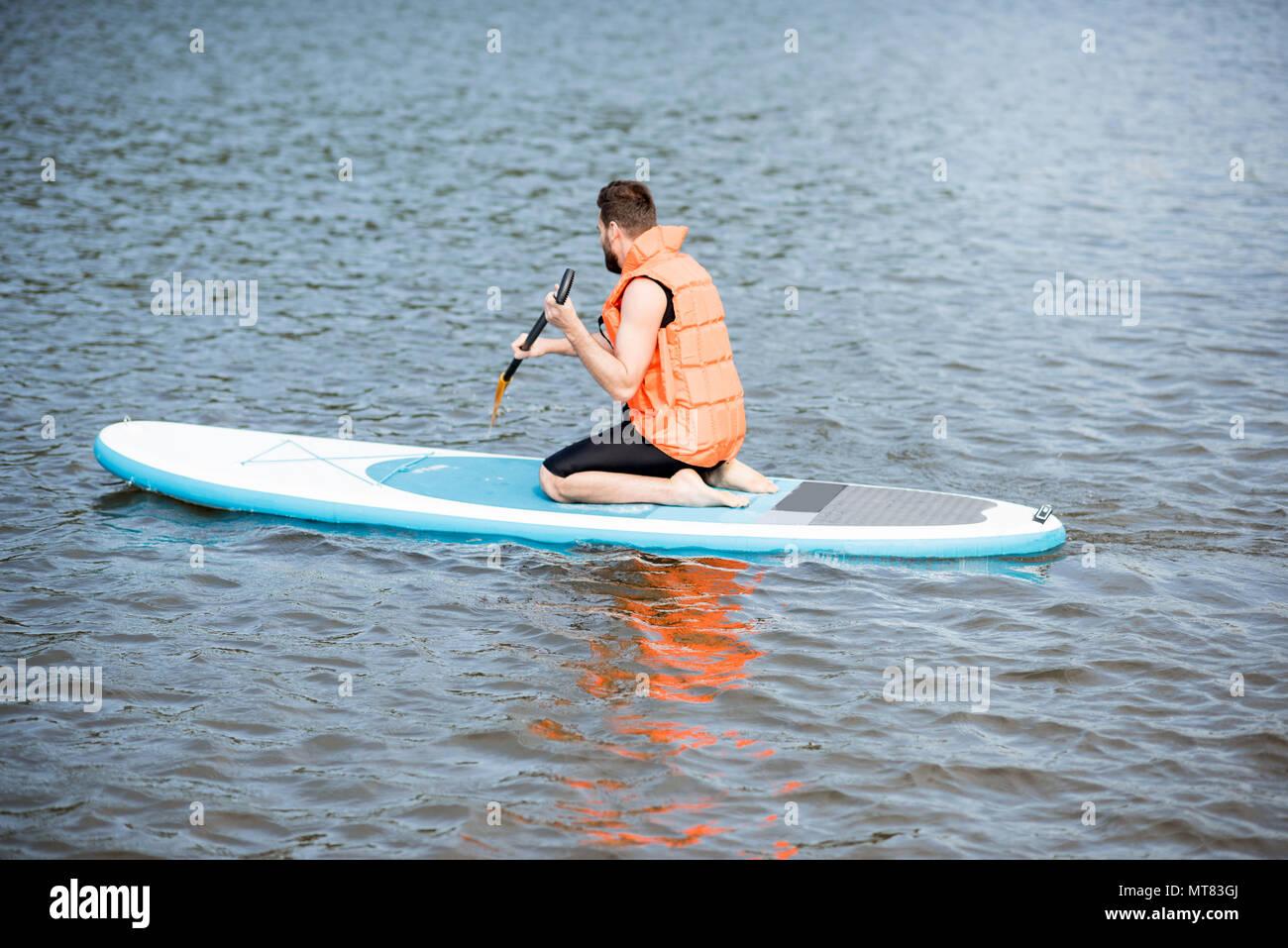 Uomo di nuoto sul paddleboard Immagini Stock