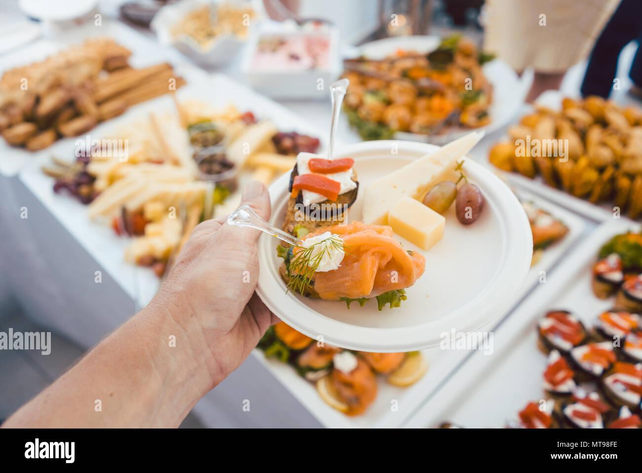 L'uomo ad aiutare se stesso sul buffet di party all'aperto prendendo il cibo Immagini Stock