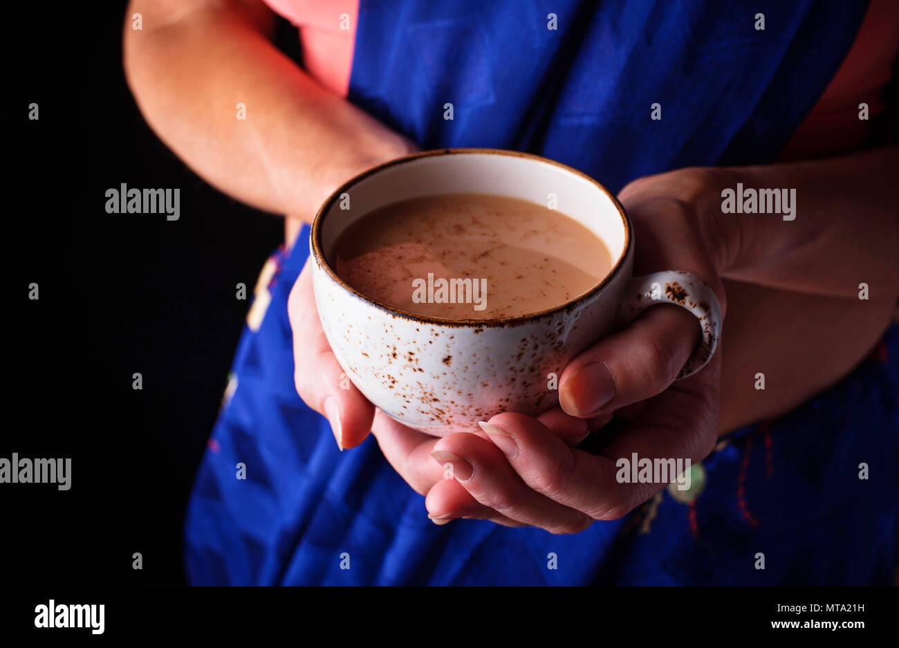 Donna in sari tenendo una tazza di masala chai tea Immagini Stock
