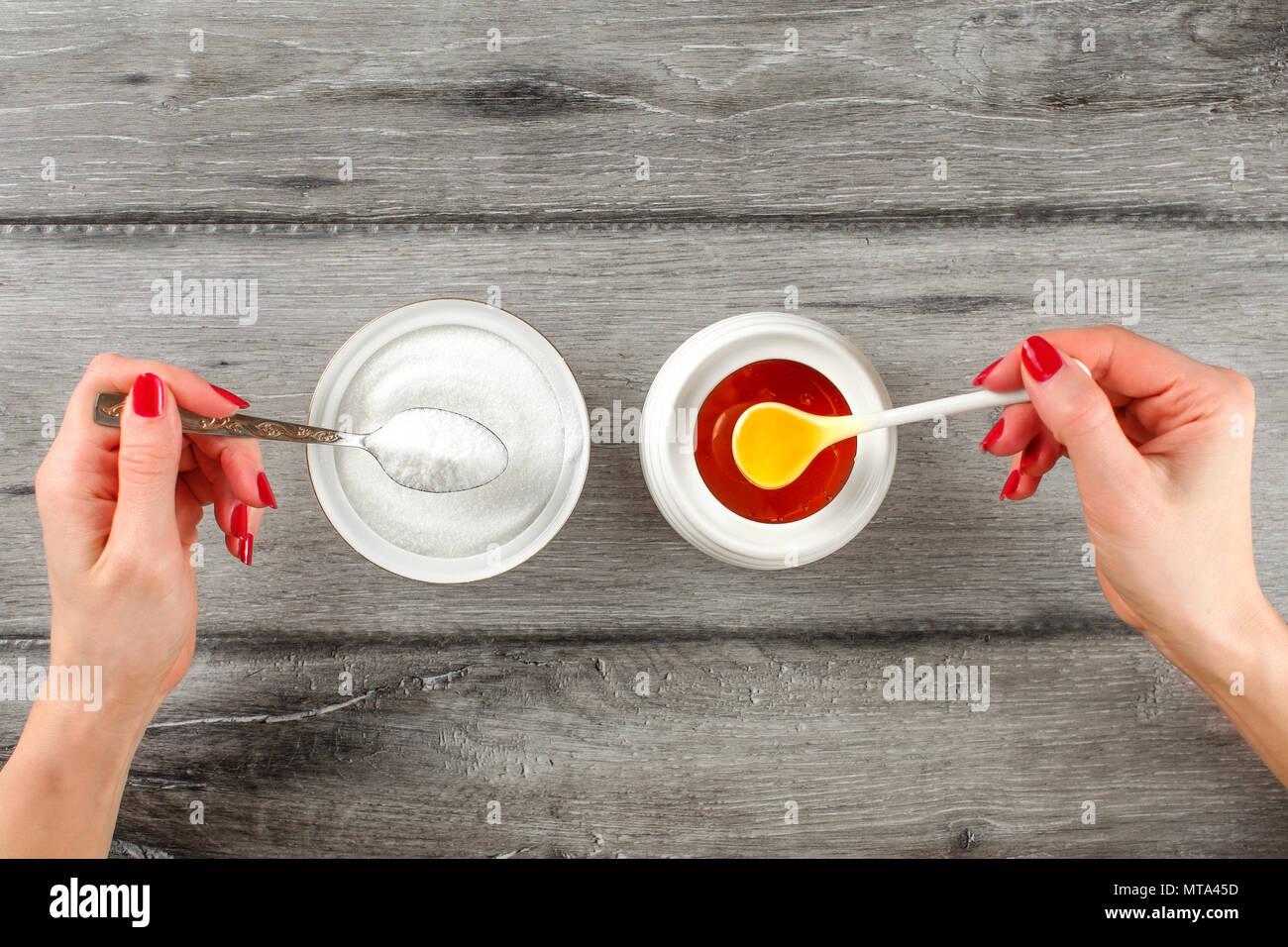 Vista dall'alto sul giovane donna mani con unghie rosse, tenendo cucchiaio colmo di zucchero e miele in altra parte. Zucchero miele vs concetto. Immagini Stock
