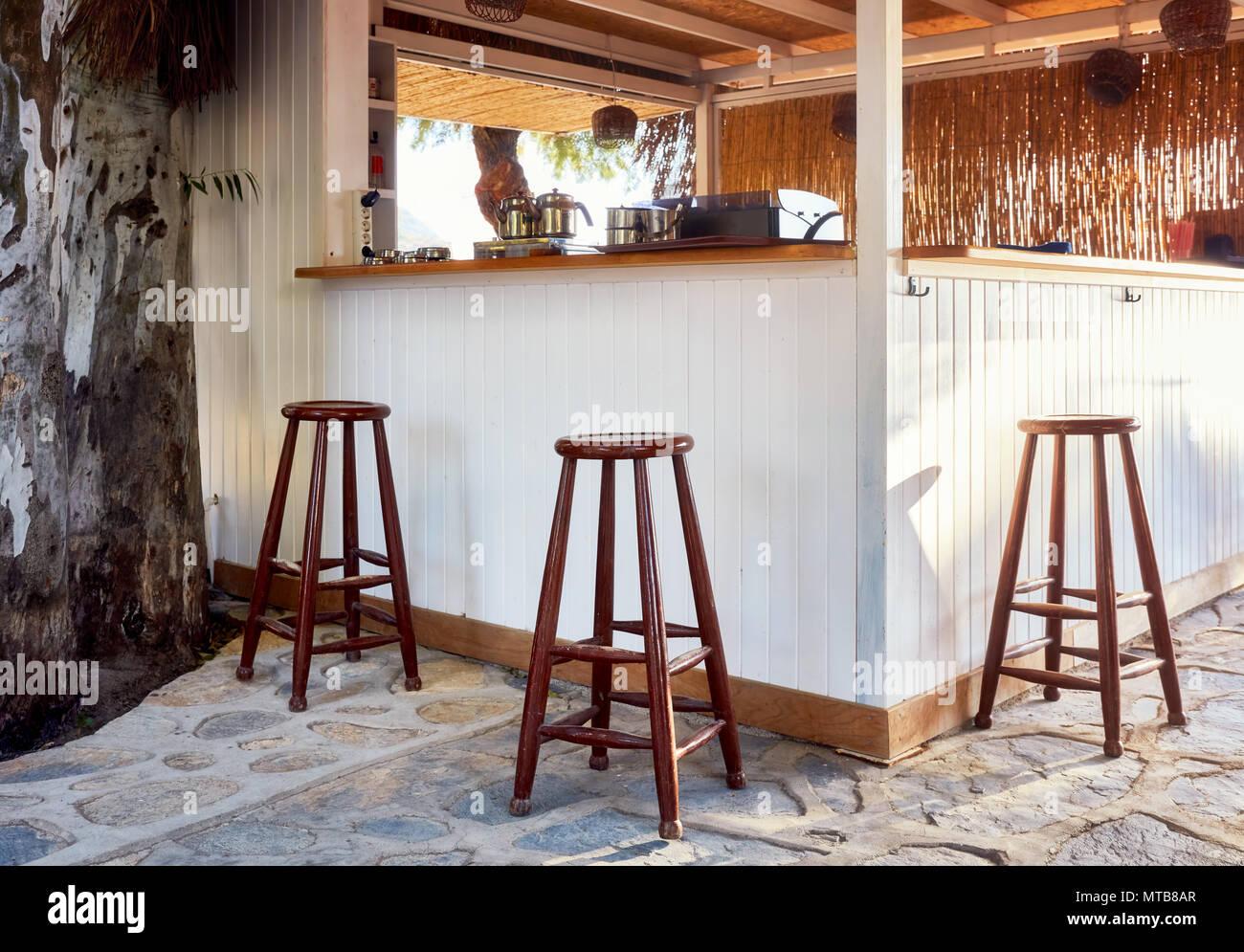 Marrone tre sgabelli in legno attorno ad una vacanza outdoor cafe