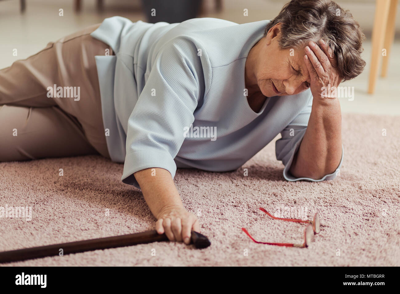 Malati senior donna con mal di testa sdraiato sul pavimento dopo la caduta verso il basso Foto Stock